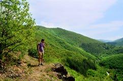 Jeune homme de touristes voyageant dans la montagne verte d'été Image stock