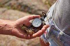 Jeune homme de voyageur recherchant la direction avec une boussole en montagnes d'été Tir de point de vue photographie stock