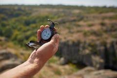 Jeune homme de voyageur recherchant la direction avec une boussole en montagnes d'été Tir de point de vue images stock