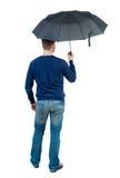 Jeune homme dedans dans un chandail blanc de knit sous un parapluie Image stock