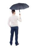 Jeune homme dedans dans un chandail blanc de knit sous un parapluie Photo stock