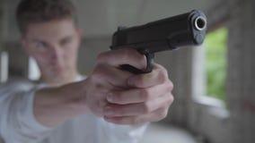 Jeune homme defocused visant avec le pistolet, ses mains secouant le plan rapproché Le type va tuer l'humain dans banque de vidéos