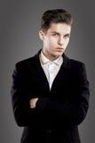 Jeune homme dernier cri Suite noire, fond gris Portrait photo libre de droits