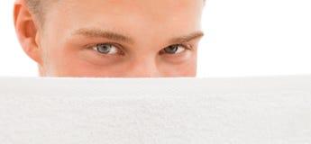 Jeune homme derrière l'essuie-main blanc Photographie stock libre de droits