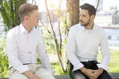 Jeune homme deux dans des chemises blanches se reposant dehors Photographie stock libre de droits