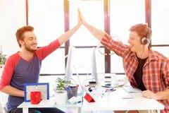 Jeune homme deux dans le bureau battant leurs mains Photographie stock