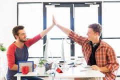 Jeune homme deux dans le bureau battant leurs mains Photo stock