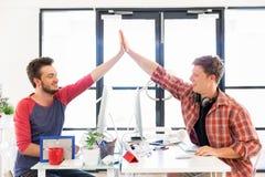 Jeune homme deux dans le bureau battant leurs mains Images libres de droits