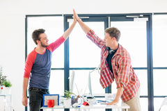 Jeune homme deux dans le bureau battant leurs mains Images stock