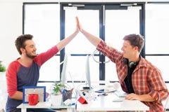 Jeune homme deux dans le bureau battant leurs mains Image stock