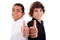 Jeune homme deux de différentes couleurs, avec le pouce vers le haut Image libre de droits