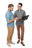 Jeune homme deux gai dicussing quelque chose sur l'ordinateur portable et le SMI Photographie stock libre de droits