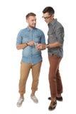 Jeune homme deux gai dicussing quelque chose sur le téléphone portable et Photos stock