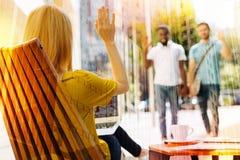 Jeune homme deux marchant et notant leur ami se reposer dans un café Photographie stock libre de droits