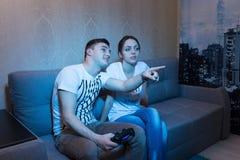 Jeune homme disant son amie au sujet du jeu à la maison Photo stock