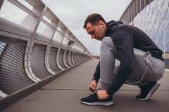 Jeune homme disposant à courir dans la ville, attachant les chaussures pulsantes images libres de droits