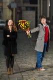 Jeune homme donnant des fleurs à sa date Photographie stock libre de droits