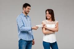 Jeune homme donnant l'argent à la femme, souriant au-dessus du fond gris Photos libres de droits