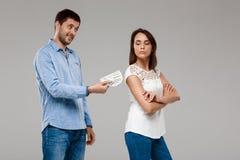 Jeune homme donnant l'argent à la femme, souriant au-dessus du fond gris Images stock
