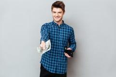 Jeune homme donnant l'argent liquide à l'appareil-photo photos libres de droits