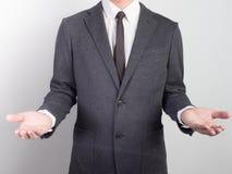 Jeune homme donnant la main vide sur le fond noir Les mains ouvrent le busin image stock