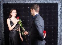 Jeune homme donnant Rose à son amie Photographie stock libre de droits