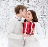 Jeune homme donnant un cadeau à son amie pour Noël Image stock