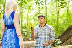 Jeune homme donnant un pissenlit de fleur à l'amie dehors Image libre de droits