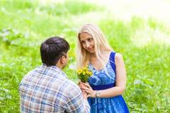 Jeune homme donnant un pissenlit de fleur à l'amie dehors Photos stock