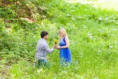 Jeune homme donnant un pissenlit de fleur à l'amie dehors Photographie stock libre de droits