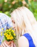 Jeune homme donnant un pissenlit de fleur à l'amie dehors Images libres de droits