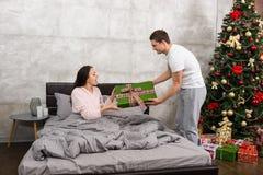 Jeune homme donnant un présent à son amie étonnée, tandis que SH Photo stock