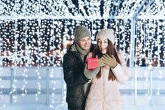Jeune homme donnant un présent à son amie dehors une soirée d'hiver Photos stock