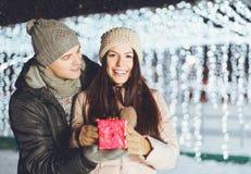 Jeune homme donnant un présent à son amie dehors une soirée d'hiver Photographie stock