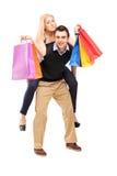 Jeune homme donnant un tour de ferroutage à une femme avec des sacs à provisions Image stock