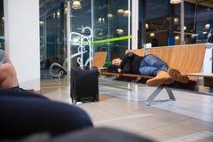 Jeune homme dormant dans le refuge d'aéroport Photo stock