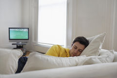 Jeune homme dormant sur le divan Photos stock