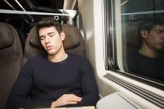 Jeune homme dormant tout en voyageant sur un train Photos libres de droits
