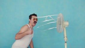 Jeune homme drôle avec un ventilateur électrique, appréciant la brise fraîche montrant des pouces sur le fond bleu MOIS lent banque de vidéos