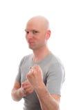 Jeune homme drôle avec des mains de tête chauve et de poing Photographie stock libre de droits