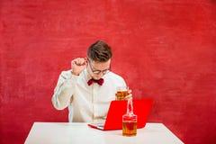 Jeune homme drôle avec l'ordinateur portable au jour du ` s de St Valentine Photographie stock libre de droits
