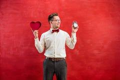 Jeune homme drôle avec le coeur et l'horloge abstraits Image stock
