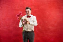 Jeune homme drôle avec les fleurs et le cadeau Photo stock