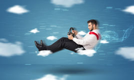 Jeune homme drôle de racedriver conduisant entre le concept de nuages Photographie stock libre de droits