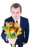 Jeune homme drôle donnant le groupe de tulipes d'isolement sur le blanc Images stock