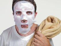 Jeune homme dr?le et malpropre appliquant le masque facial de beaut? regardant au miroir ?tonn? et horrifi? dans le concept vieil images stock