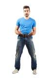 Jeune homme drôle tirant sa ceinture Image stock