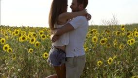 Jeune homme embrassant et tournant son amie dans le concept de champ des couples heureux banque de vidéos