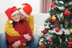 Jeune homme embrassant l'amie près de l'arbre de Noël Image stock