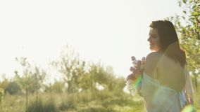 Jeune homme embrassant son épouse avec des pommiers à l'arrière-plan banque de vidéos